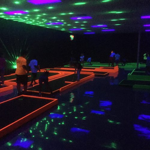 people playing glow in the dark golf